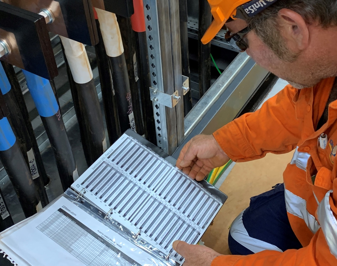 man looking at sleeved cable markers Queensland Australia , project packaging